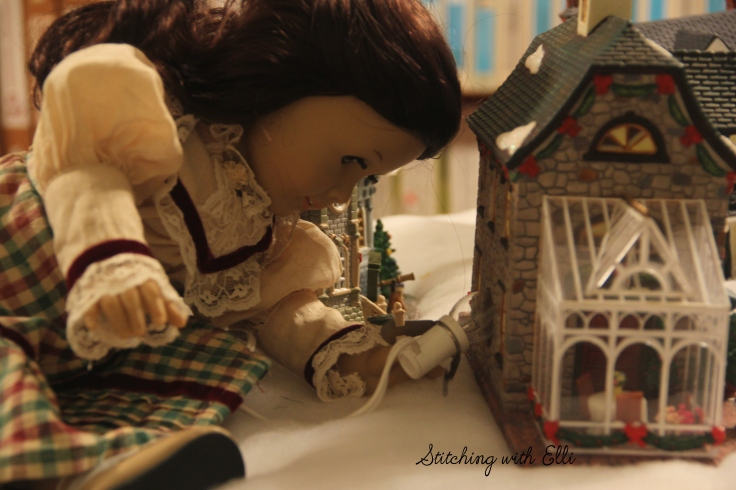 Setting up a Christmas village! Ruthie is putting in the lights- by Stitching with Elli